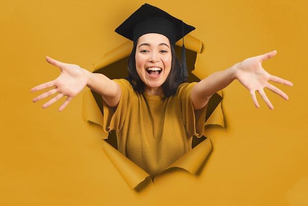 Une fille asiatique heureuse avec un chapeau de graduation sort d'un trou sur un fond de papier jaune
