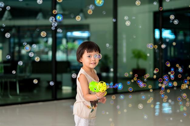 Fille asiatique heureuse enfants jouant avec des bulles de savon.