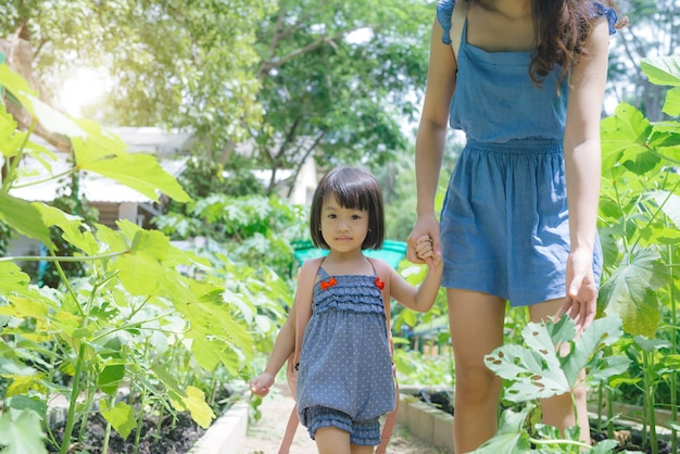 Fille asiatique heureuse jardinant avec sa mère