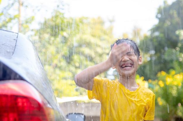 Fille asiatique heureuse lavant la voiture sur les éclaboussures d'eau et la lumière du soleil à la maison