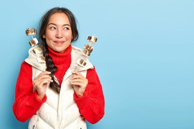 Une fille asiatique heureuse tient de la guimauve rôtie sur un feu de camp, vous suggère une friandise, passe le dimanche à pique-niquer dans la forêt, porte un pull en tricot rouge chaud et une veste blanche, isolé sur un mur bleu