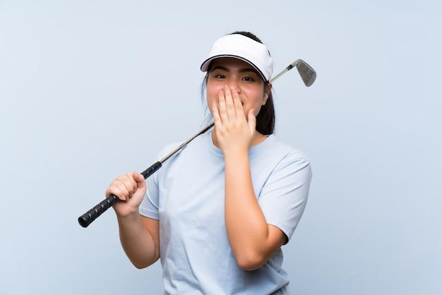 Fille asiatique jeune golfeur sur fond bleu isolé avec une expression faciale surprise