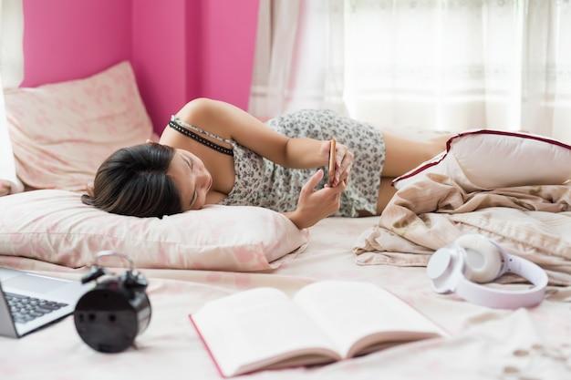 Fille asiatique joue smartphone sur lit