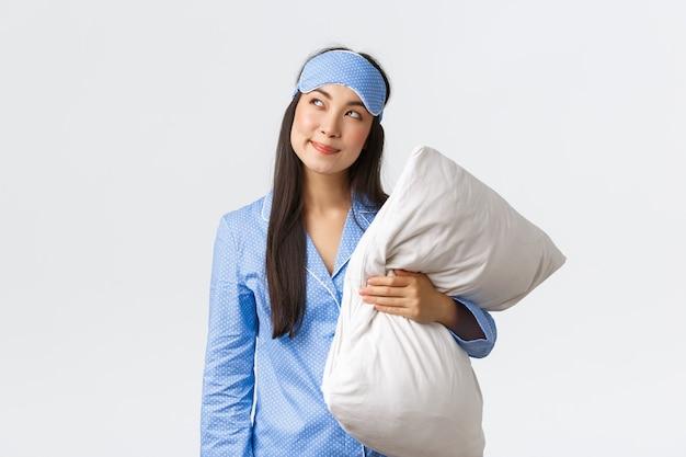 Fille asiatique kawaii rusée et réfléchie en pyjama bleu et masque de sommeil, tenant un oreiller et