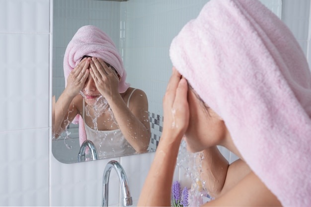 Fille asiatique lave le visage.