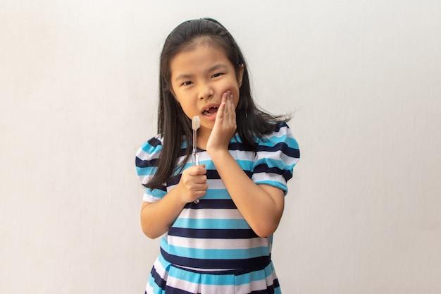 Fille asiatique a un mal de dents tenant une brosse à dents