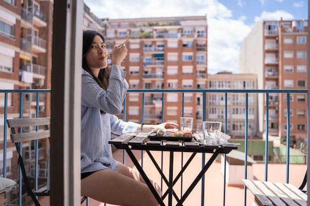 Fille asiatique, manger des sushis sur le balcon, assis sur une chaise sur la terrasse dans des vêtements décontractés