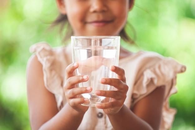 Fille asiatique mignonne aime boire de l'eau et tenant un verre d'eau douce
