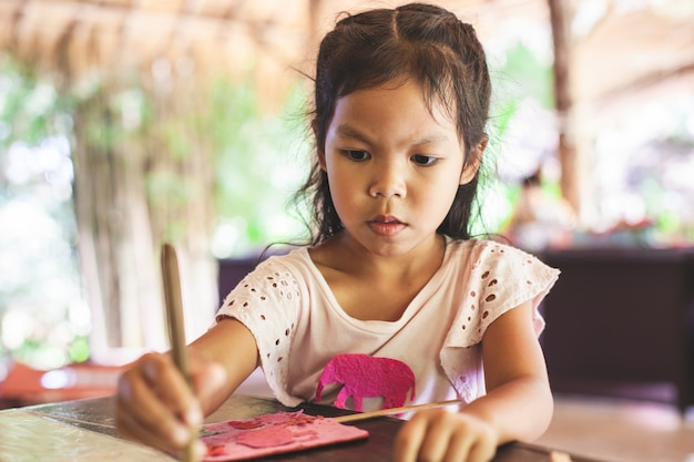 Une fille asiatique mignonne fait un travail manuel avec du papier recyclé à partir du caca d'éléphants