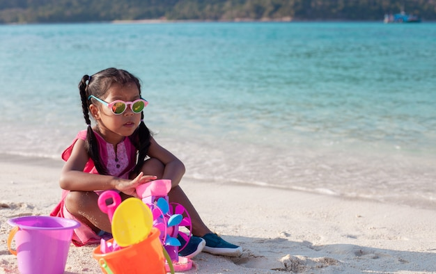 Fille asiatique mignonne fille lunettes de soleil s'amuser à jouer avec du sable sur la plage