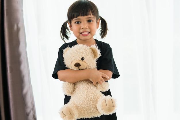 Fille asiatique avec ours en peluche regarde la caméra.