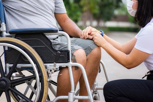 Fille asiatique parlant et réconfortant père lié en fauteuil roulant
