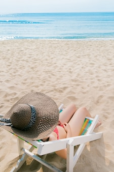 Fille asiatique sur la plage, elle s'assoit sur une chaise de plage et se détend.