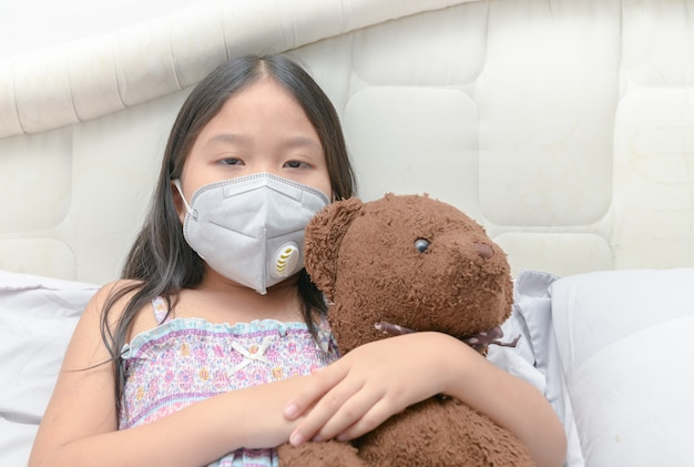 Fille asiatique portant un masque anti-poussière sur le lit,