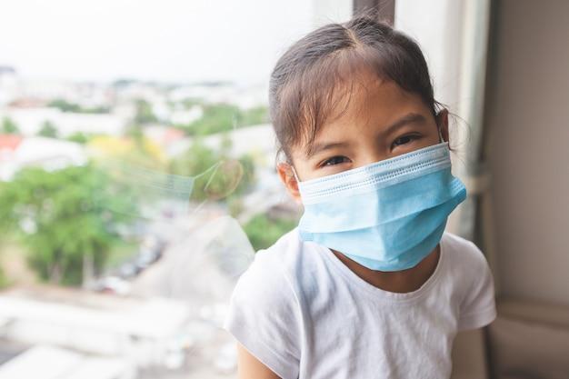 Fille asiatique portant un masque de protection et rester à la maison