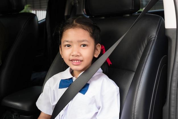 Fille asiatique porter l'uniforme scolaire s'asseoir dans la voiture