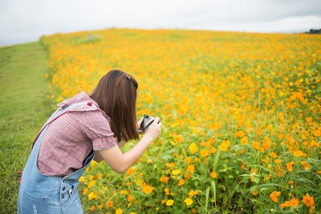 Fille asiatique prendre photo fleurs jaunes, concept de voyage