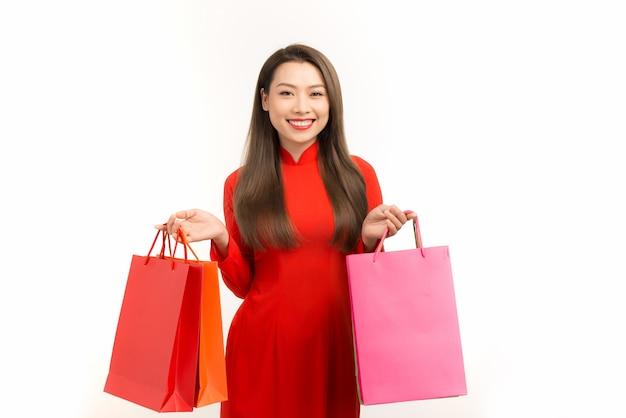 Fille asiatique en robe ao dai vietnamienne avec sac à provisions isolé sur blanc.