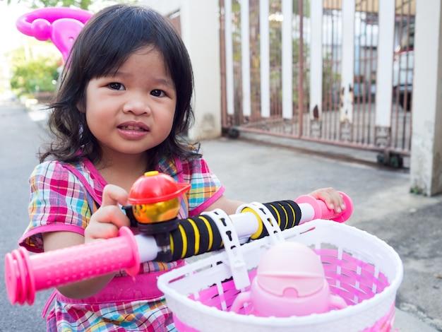 Fille asiatique sur une robe rose avec un nouveau vélo rose