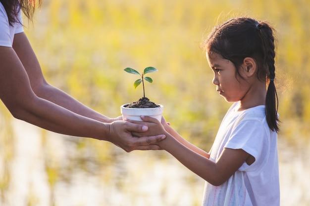 Fille asiatique et sa mère tenant de jeunes semis dans le pot de fleurs pour préparer la plantation au sol