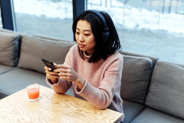 Fille asiatique seule dans la ville est assise dans un café et écoute de la musique. profiter de la musique dans un lieu public