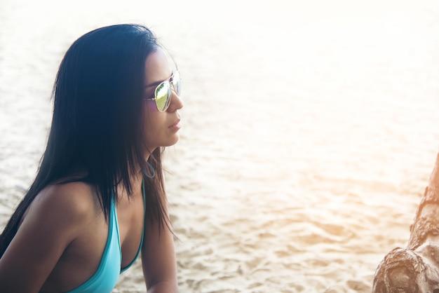 Fille asiatique sexy en maillot de bain bleu avec des lunettes de soleil posant sur un été de la plage