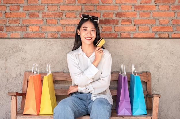 Fille asiatique souriante avec une carte de crédit et des sacs à provisions profitant de l'expression de détente shopping