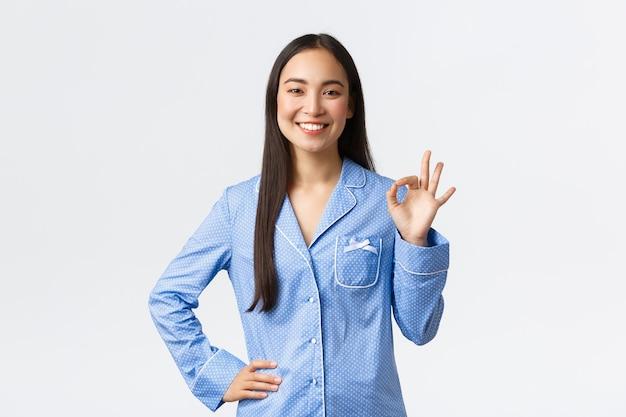 Une fille asiatique souriante et heureuse en jammies bleus montrant un geste correct en comme ou en soutien, dites ok comme recommande un produit de grande qualité, garantissez tout sous contrôle, disant tout bien, fond blanc