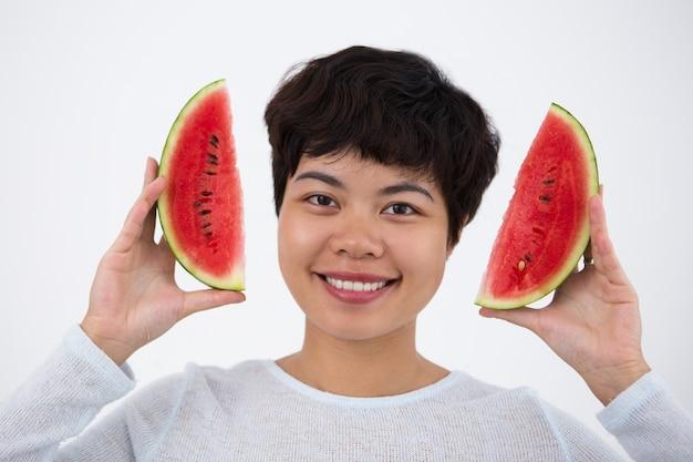 Fille asiatique souriante tenant des tranches de pastèque