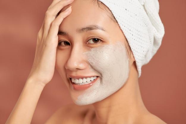 Fille asiatique de spa appliquant le masque facial d'argile. soins de beauté. sur fond bleu.