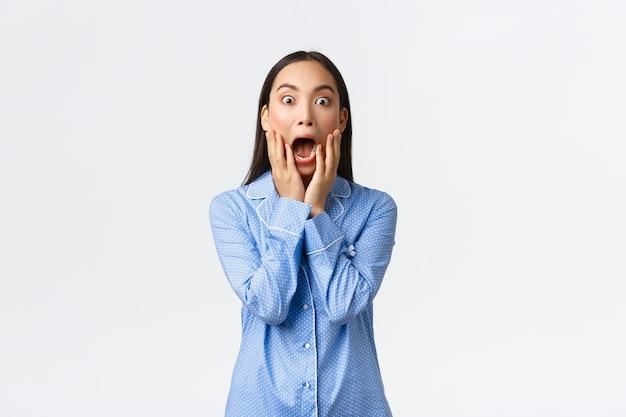 Fille asiatique surprise et choquée en pyjama bleu hurlant de crainte et d'étonnement, tenant les mains sur la bouche ouverte et regardant la caméra impressionné, debout sur fond blanc.