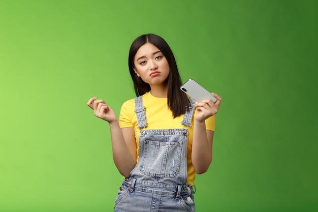 Une fille asiatique urbaine cool et indifférente qui s'ennuie perd son temps en vacances d'été seule à jouer à l'inter...