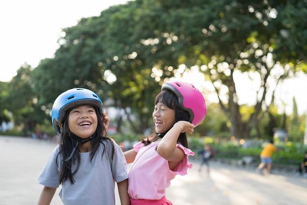 Fille asiatique va sur ses patins à roues alignées