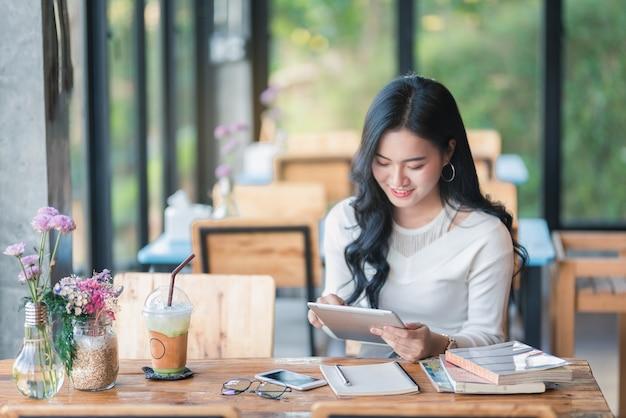 Fille d'asie à l'aide d'une tablette au café