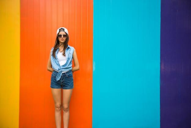 Fille assez cool en lunettes de soleil et casquette debout contre.