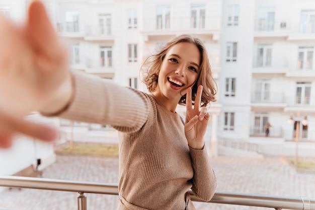 Fille assez excitée en pull faisant selfie au balcon. femme brune jocund en tenue marron debout à la terrasse.