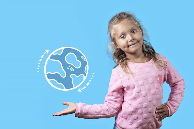 Une fille assez joyeuse avec des fossettes sur les joues et des cheveux bouclés sourit. sur sa main qui tourne la planète terre