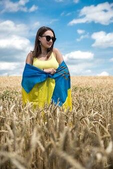 Fille assez mince avec le drapeau jaune-bleu de l'ukraine dans le champ de blé. mode de vie