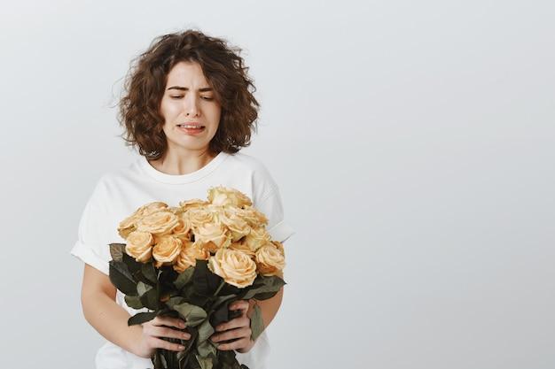 Fille assez sceptique grince des dents en regardant les fleurs, n'aime pas les roses, ne pas être impressionnée