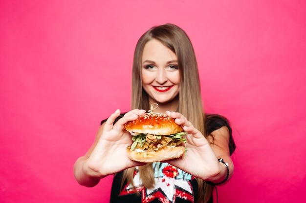 Fille assez souriante avec hamburger dans les mains au premier plan.