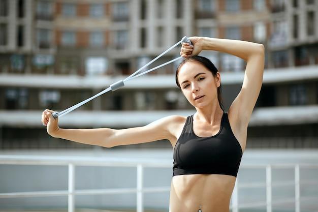 Fille assez sportive faisant de l'exercice avec les mains avec une bande de résistance élastique. espace pour le texte