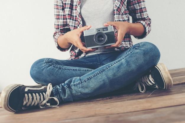 Fille assis en tailleur avec une vieille caméra