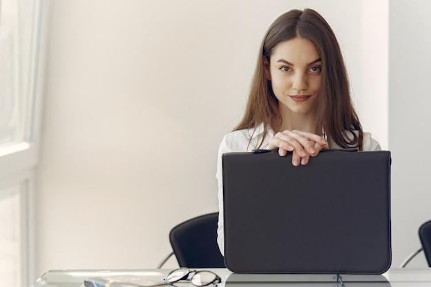 Fille assise au bureau avec un ordinateur portable