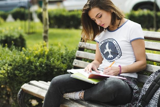 Fille assise sur banc d'écriture dans un cahier