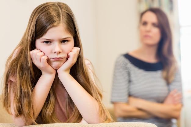 Fille assise bouleversé avec sa mère dans le salon