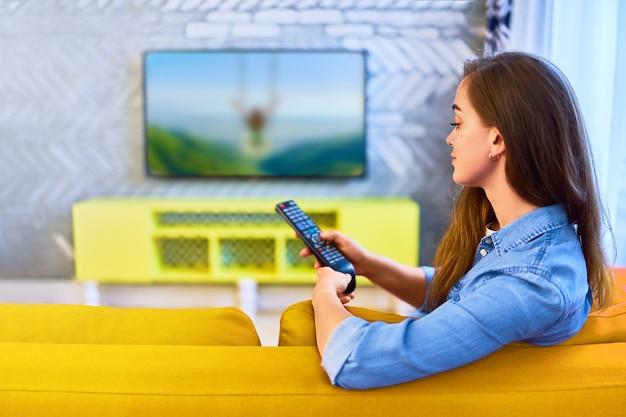 Fille assise sur un canapé, change de chaîne sur la télécommande et regarde la télévision seule à la maison