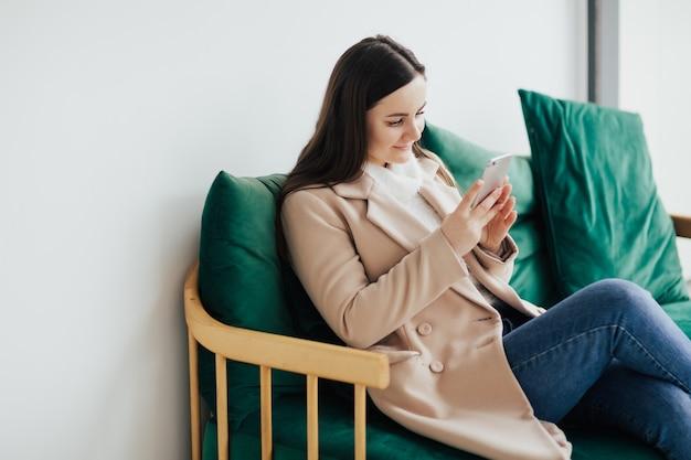 Fille assise sur le canapé dans le café avec smartphone