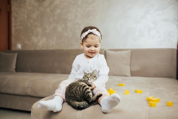 Fille assise sur le canapé et joue avec des cubes jaunes