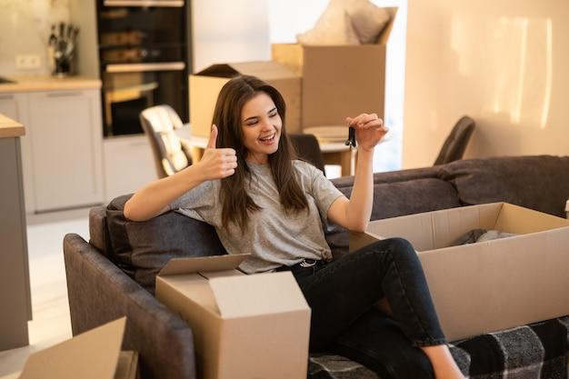 Fille assise sur un canapé, montrant le geste du pouce vers le haut et la clé de la nouvelle maison. souriante jeune femme européenne. boîtes en carton avec des choses. concept de déménagement dans un nouvel appartement. intérieur du studio