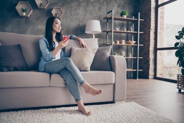 Fille assise sur un canapé en regardant le téléphone